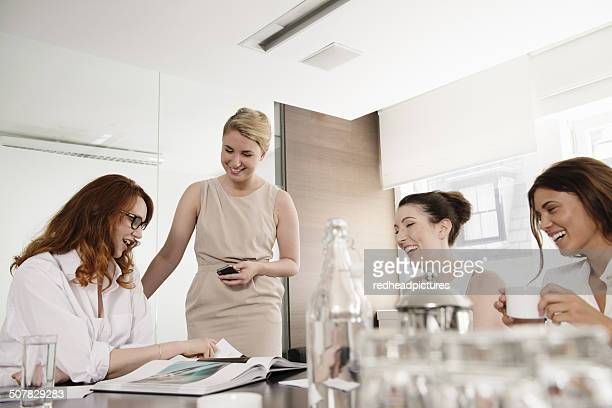 Four businesswomen looking at portfolio in conference room