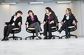 Four businesswomen sitting in office chairs