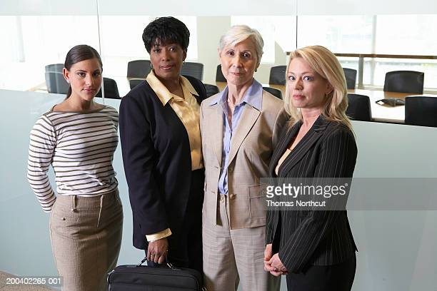 Four businesswomen standing outside boardroom, portrait