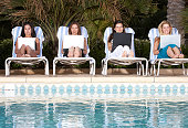 Four businesswomen using laptop at poolside