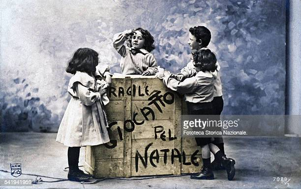 Four children around a wooden box with the inscription 'Fragile toys for Christmas' Photography slightly handcoloured Italy Turin 1905
