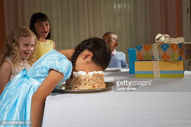 Four children (5-8) at table, laughing at girl with face in cake