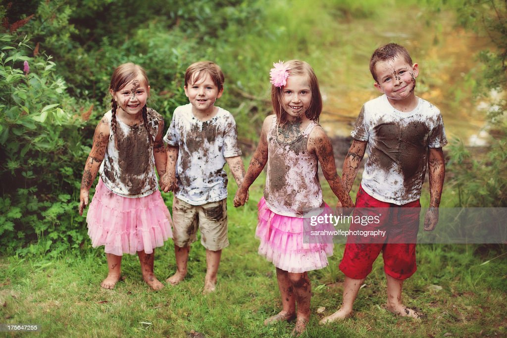 Four children covered in mud