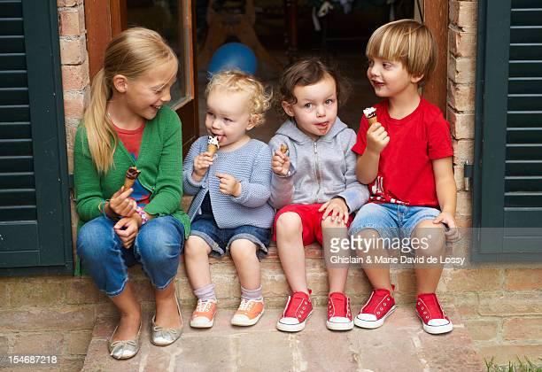 Four children eating ice cream, sitting