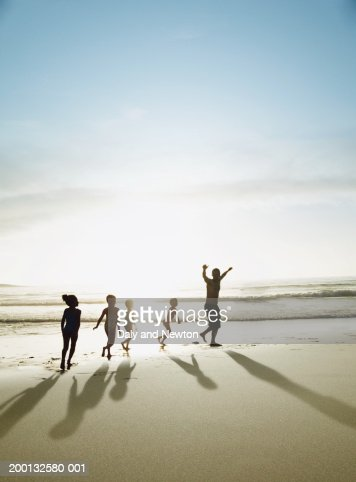 Four children (4-7) following man on beach, sunset, silhouette : Stock Photo