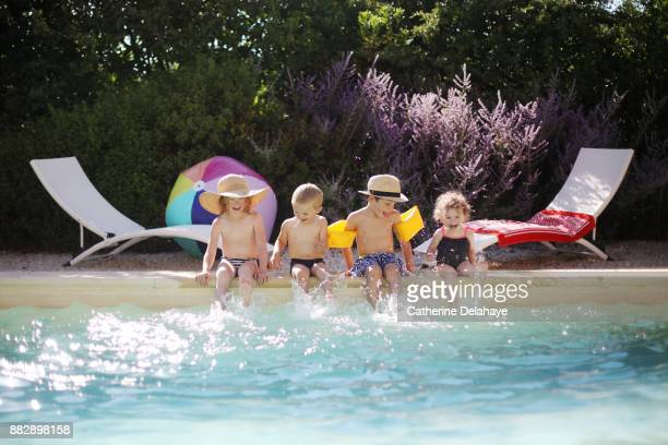 Four children having fun by the swimming pool