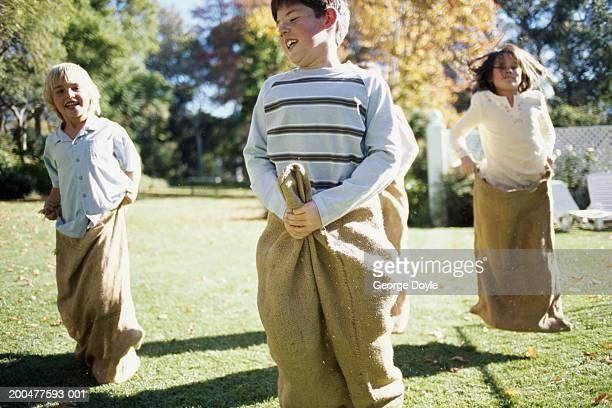Four children (7-10) having sack race in garden, smiling