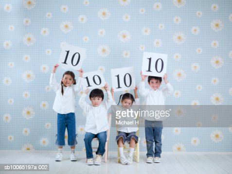 Four children (4-5 years) holding score boards above heads, studio shot, portrait