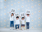 Four children (4-5 years) holding score boards above heads, studio shot, portrait