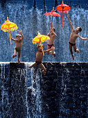 Four children play and jump in the storied river with their colorful umbrellas