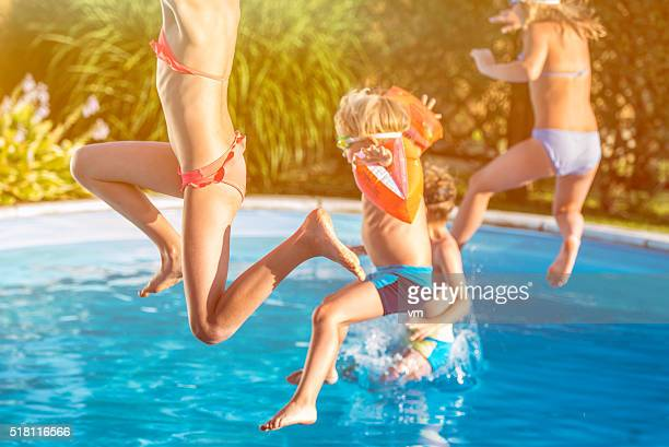Four children jumping into a pool