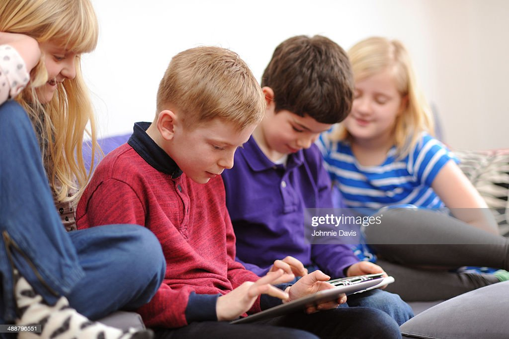 Four children looking at ipads : Stock Photo