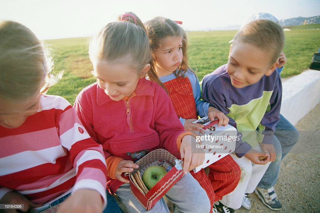 Four children (4-7) looking at lunch boxes, outdoors