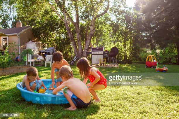Four children playing outside in a paddling pool in the garden