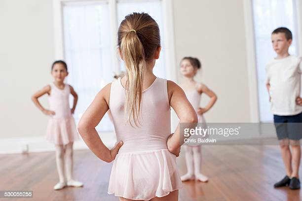 Four children practicing ballet with hands on hips in ballet school