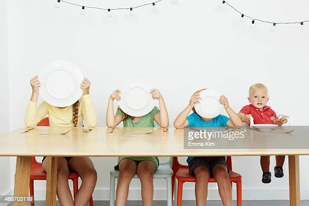 Four children sitting at table, three covering faces with plates