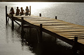 Four children (7-9) sitting on dock by lake, back view.