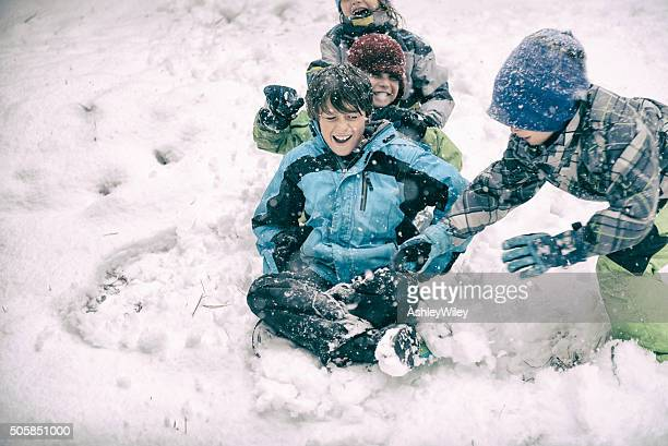 Four children sledding and playing during a big snow storm