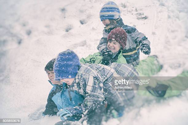 Four children sledding in a snow storm