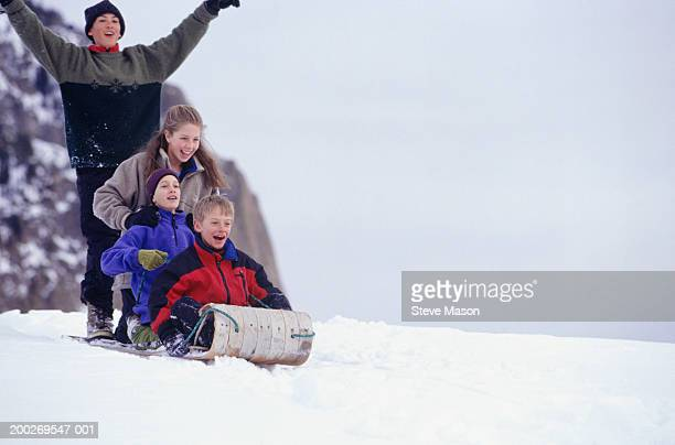 Four children (8-9) sledding