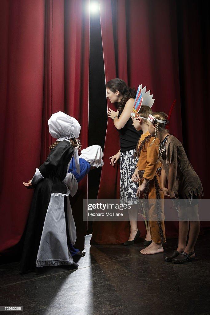 Four children (7-9) with teacher peeking through theatre curtains