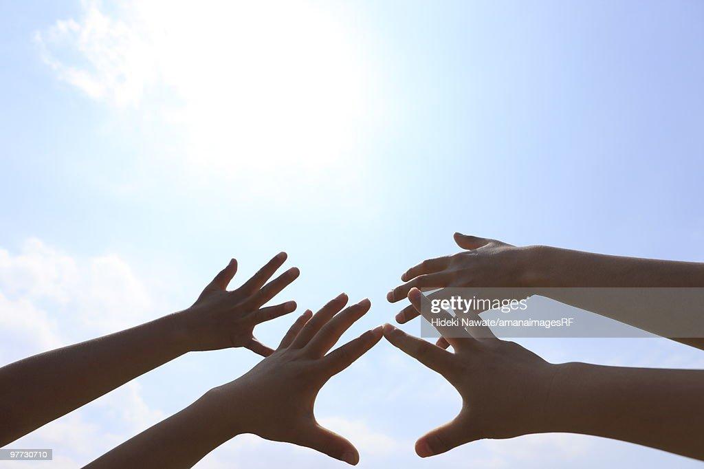 Four children's hands reaching towards sky : Stock Photo