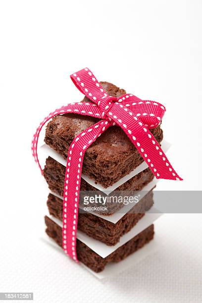 Four chocolate brownies stacked and tied with a bow