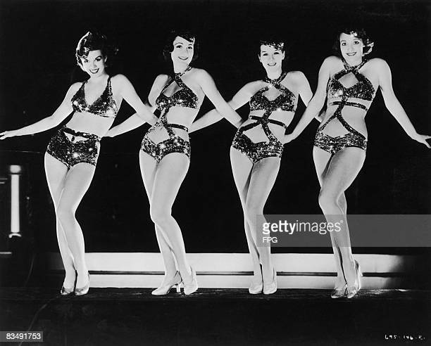 Four chorus girls wearing sparkly costumes dancing in a row circa 1935