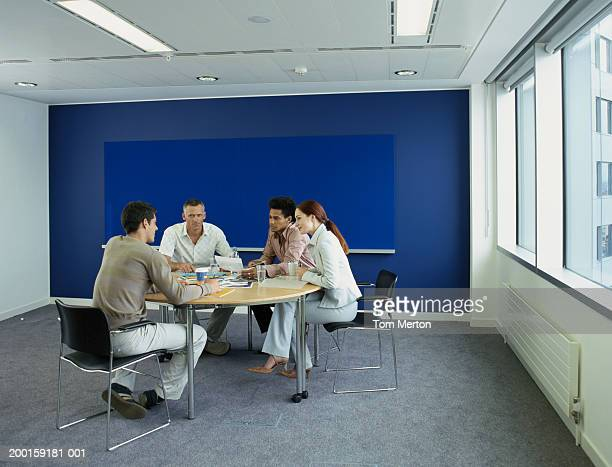 Four colleagues at table in meeting room