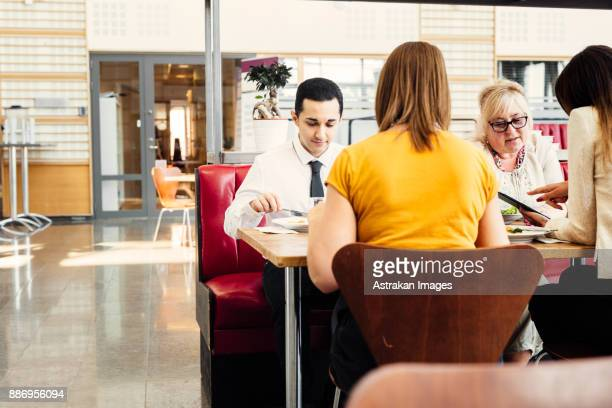 Four colleagues eating lunch in cafeteria