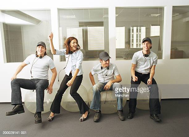 Four colleagues wearing headphones sitting on exercise balls
