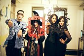 Four college students in costume pose for a picture one male student is dressed as a zombie one girl is dressed in a witch costume with the nose of a...