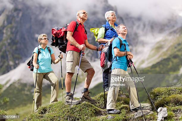four colorful dressed senior hikers
