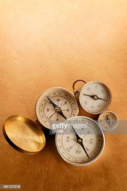 Vier Kompass auf einer warmen, strukturierten Hintergrund