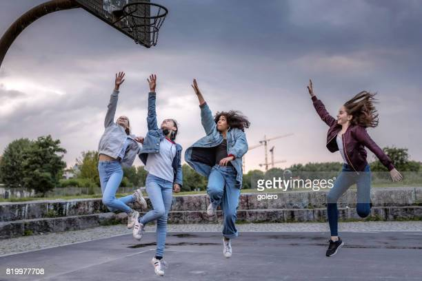 four cool teenage girls jumping on street ball court