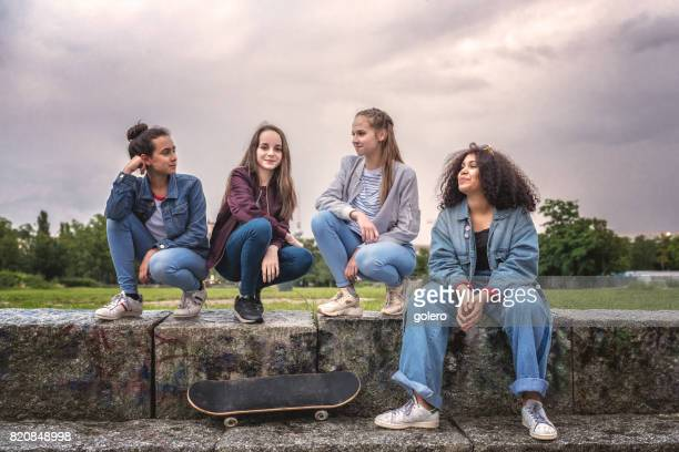 four cool teenage girls sitting on stairs outdoors