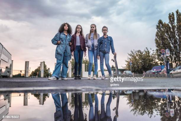 four cool teenage girls standing outdoors