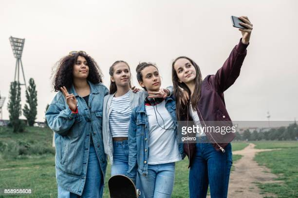 four cool teenage girls taking selfie outdoors