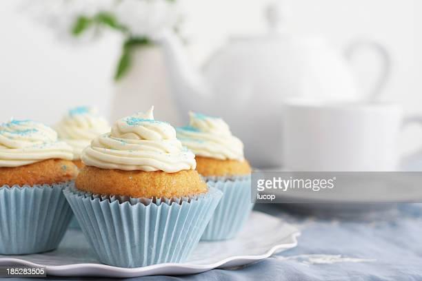 Bleu cupcakes vanille avec glaçage et théière et tasses en arrière-plan