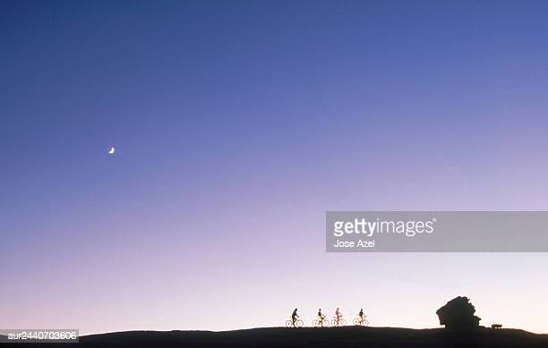 Four cyclists riding the bicycle on the top of the plain, Utah, USA.