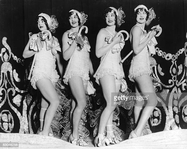 Four dancers wearing frilly outfits and carrying shepherd's crooks during a performance circa 1930