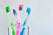 Four different colored toothbrushes in toothbrush holder.