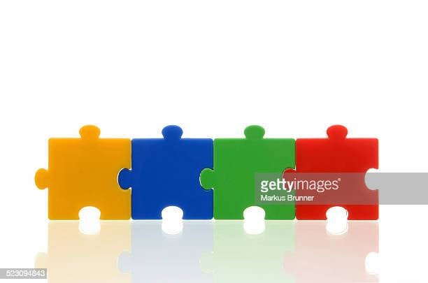 Four different coloured puzzle pieces, connected, symbolic image, team, series