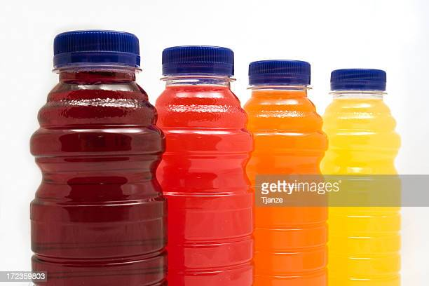 Four different juice bottles in a row with white background