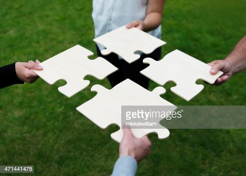 Four different people connecting large puzzle pieces