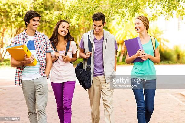 Quatre différents étudiants marchant dans campus