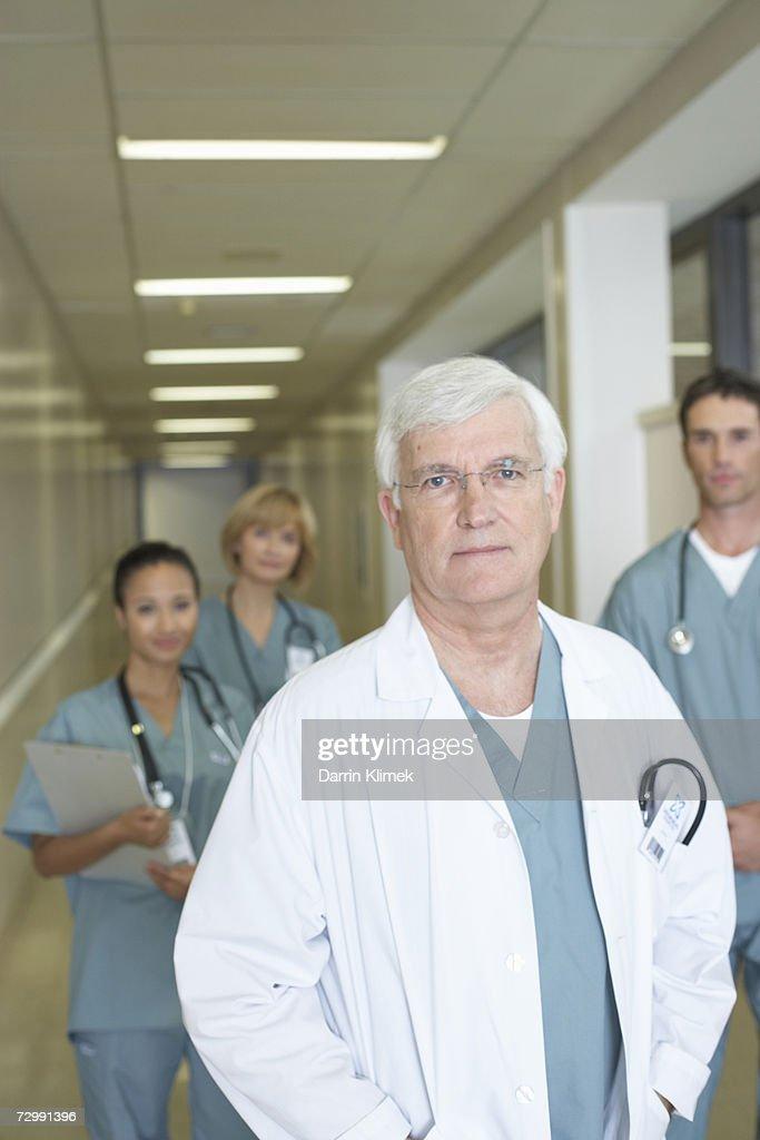 Four doctors standing in hospital corridor, smiling, portrait : Stock Photo