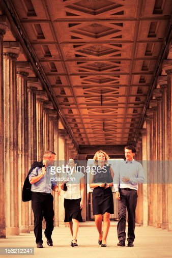 Four Elegant People Walking in Columns Passage - Sepia : Stock Photo