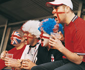 Four English Supporters in a Line Holding Pint Glasses of Lager Cheering From the Stands