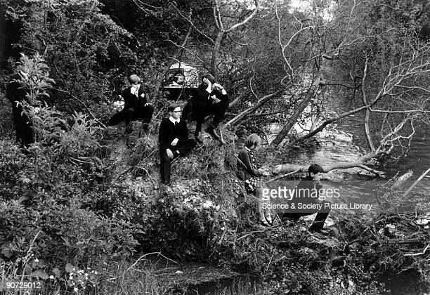 Four Eton schoolboys in uniforms sitting with a young girl on a wooded riverbank Photographer Tony RayJones created most of his images of the British...